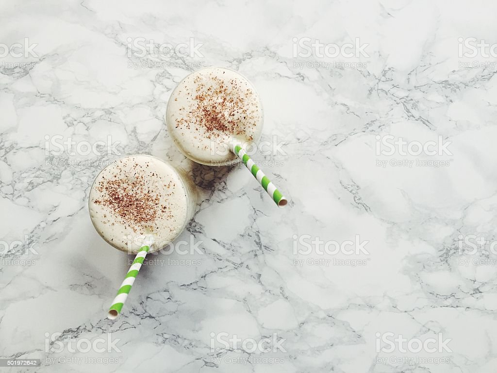 Two glasses of homemade eggnog on a kitchen countertop, with green...