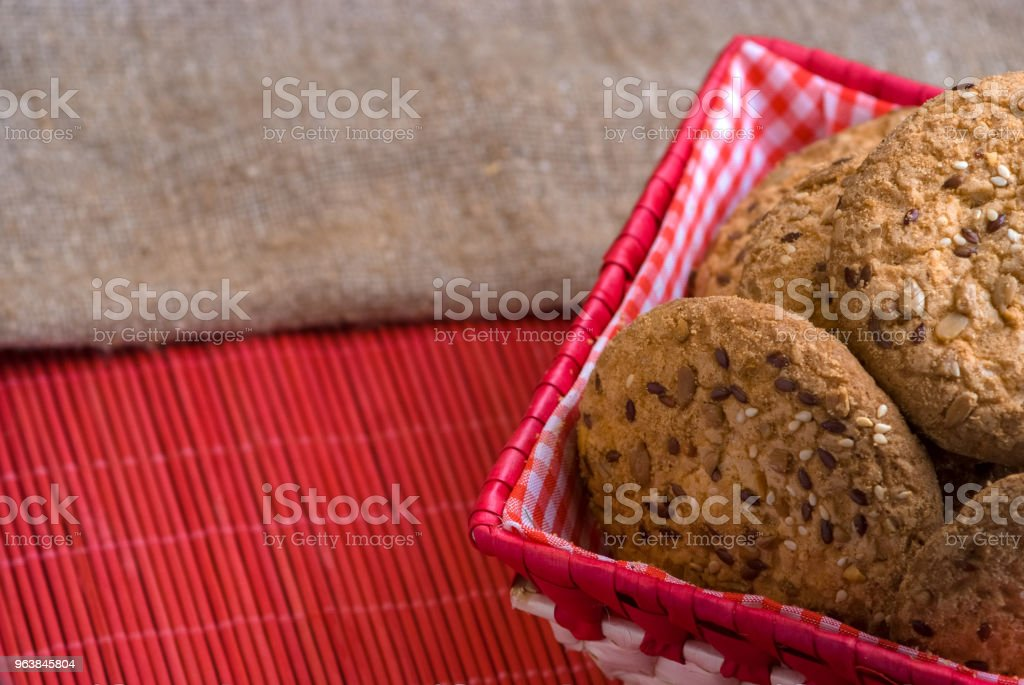 homemade oat cookies with sunflower seeds in and near red checkered basket on black wooden table - Royalty-free Bakery Stock Photo