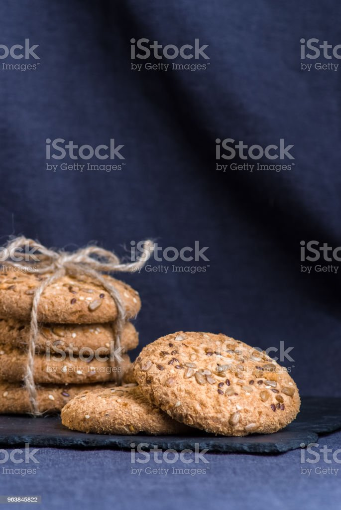 homemade oat cookies with sunflower seeds on shale board and dark blue textile background - Royalty-free Bakery Stock Photo