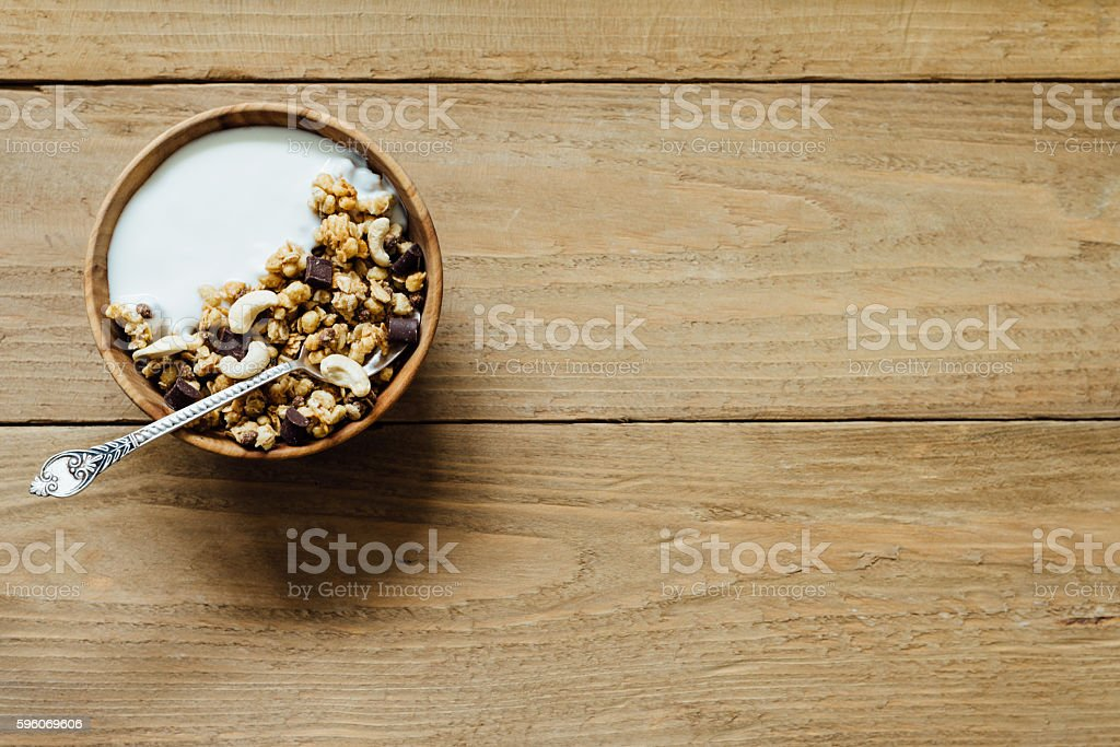 Homemade oatmeal chocolate granola with yogurt in wooden bowl royalty-free stock photo