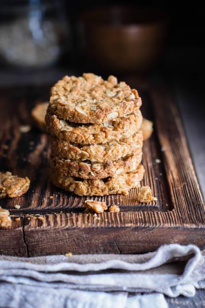 hausgemachte haferkekse auf holzbrett auf alten tabellenhintergrund. gesunde ernährung-snack-konzept. raum zu kopieren / - hafer cookies stock-fotos und bilder