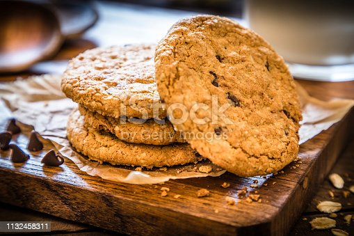 Pile of homemade oatmeal cookies with chocolate chips upon a cutting board on rustic wooden table. Cookies are surrounded by oat flakes, oat spikes and chocolate chips. Main focus is on cookies and in the defocused background is a glass full of milk. Low key DSLR photo taken with Canon EOS 6D Mark II and Canon EF 24-105 mm f/4L