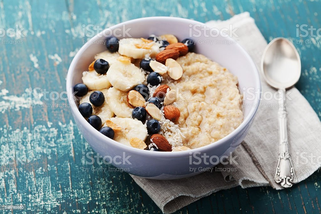Homemade oatmeal porridge with banana, blueberries, almonds, coconut and caramel stock photo