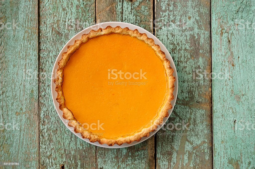 Homemade oldfashioned open round pumpkin pie on old painted wood stock photo