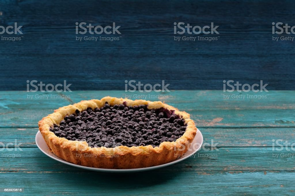Homemade open pie with wild blueberries on blue wooden table stock photo