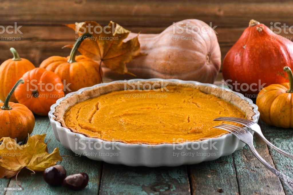 Homemade open pumpkin pie for Thanksgiving dinner served with decorative pumpkins, chestnuts and dry marple leaves stock photo