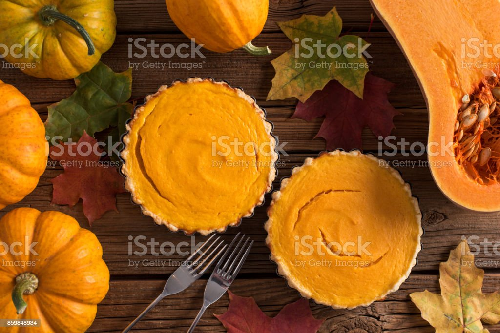 Homemade open pumpkin pies for Thanksgiving served with forks, bright orange pumpkins and marple leaves on old wooden background stock photo