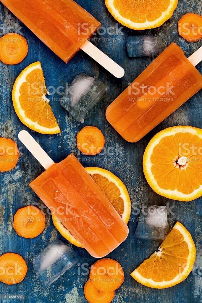Homemade orange and carrot popsicles with turmeric, honey and ginger stock photo