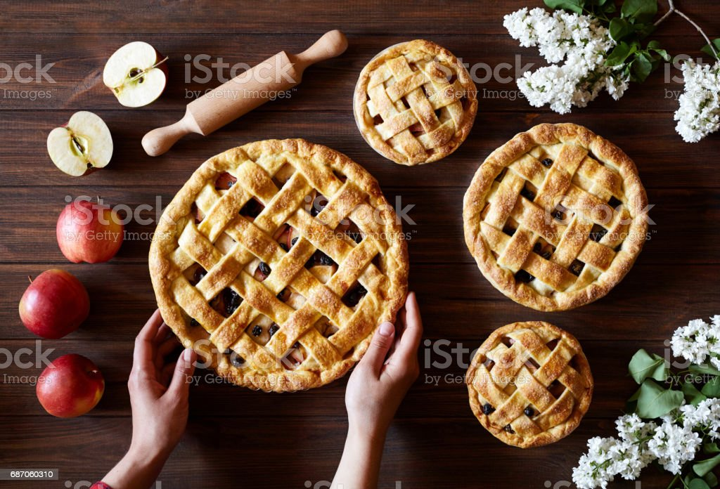Homemade organic apple pie hold female hands on dark wooden kitchen table with flowers and apples. Traditional dessert on Independence Day. stock photo