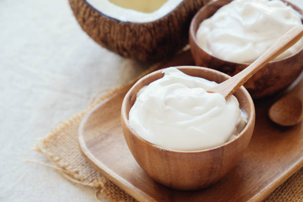 homemade organic coconut greek yogurt in wooden bowl stock photo