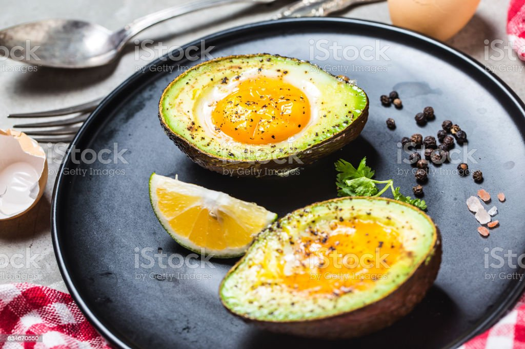 Homemade Organic Egg Baked in Avocado with Salt and Pepper stock photo