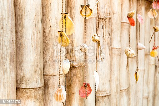 istock Homemade ornaments from sea shells on bamboo fence 812622170