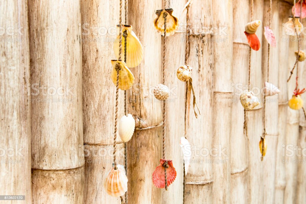 Homemade ornaments from sea shells on bamboo fence stock photo