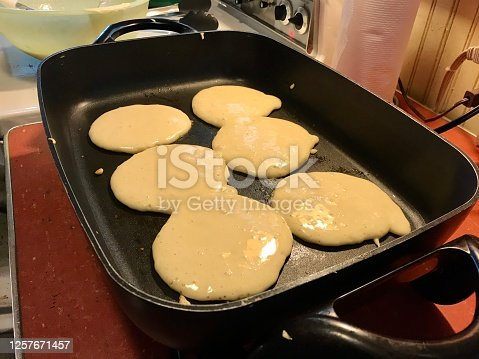 Hot griddle in the kitchen with six fresh pancakes