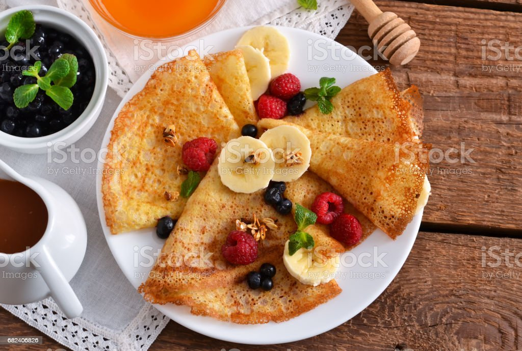 Homemade pancakes with banana, berries and honey for breakfast on a wooden background royalty-free stock photo