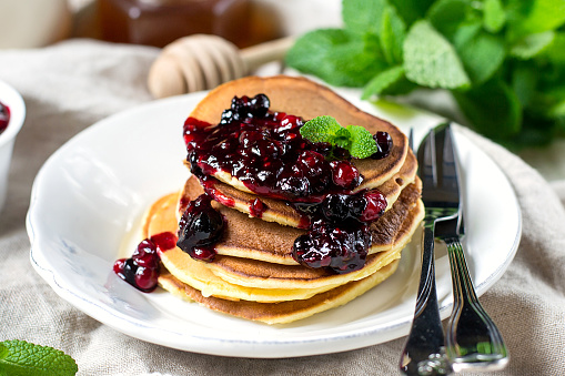Homemade pancakes with berry sauce coulis and mint