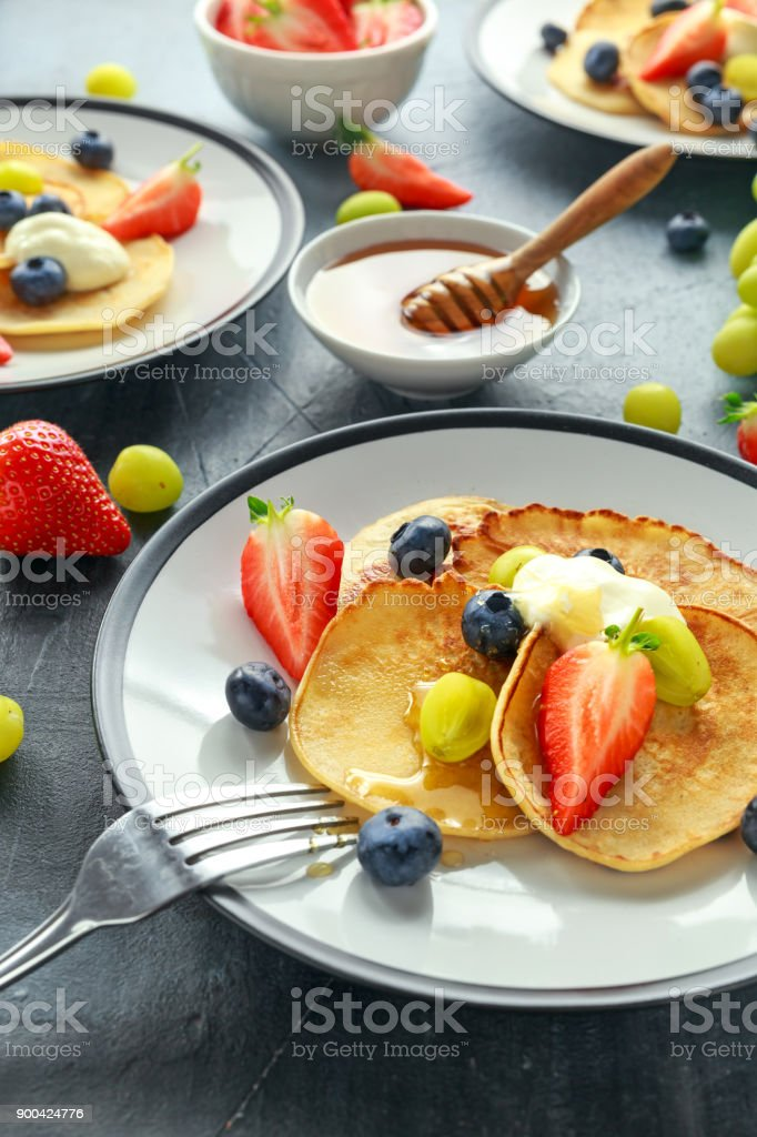 Homemade Pancakes with Blueberry, Strawberry, green Grape and honey syrup. served on plate stock photo