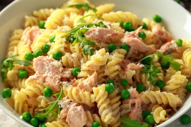 hausgemachte pasta fusilli mit lachs, grünen erbsen, parmesankäse und zitrone. naht. gesunde ernährung - spaghetti mit lachs stock-fotos und bilder