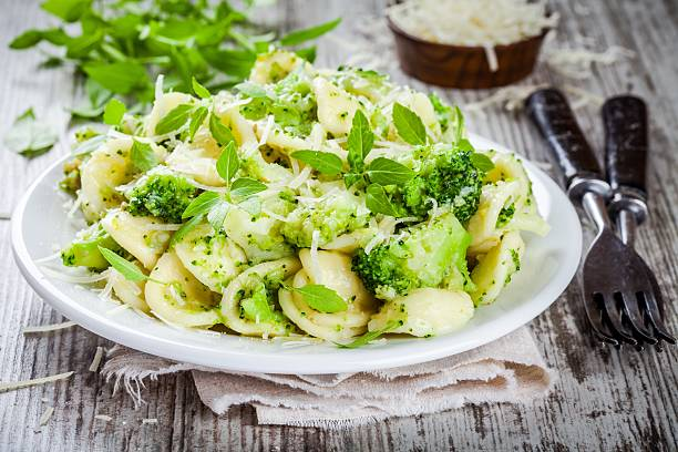 homemade pasta orecchiette with broccoli, Parmesan cheese and basil homemade pasta orecchiette with broccoli, Parmesan cheese and basil on a wooden table orecchiette stock pictures, royalty-free photos & images