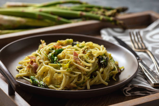 Homemade pasta with bacon, parmesan and asparagus. stock photo