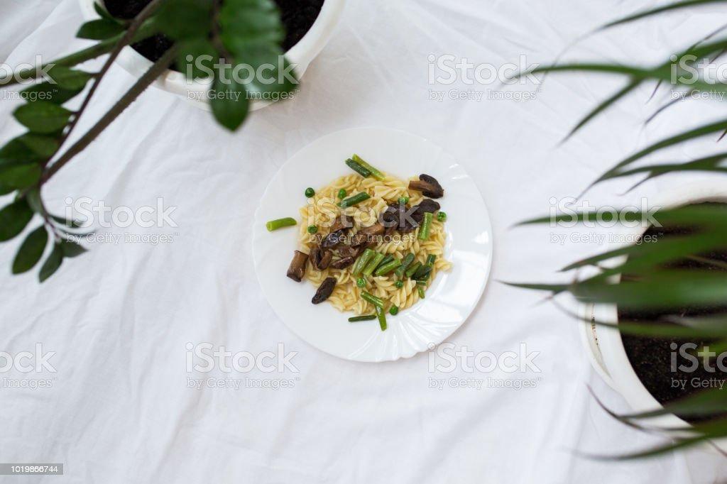 Des pâtes aux champignons et légumes: haricots et petits pois dans une assiette. - Photo