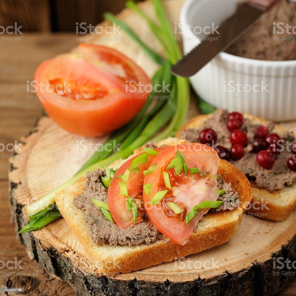 Homemade pate on white toasts with tomatoes, scallion stock photo