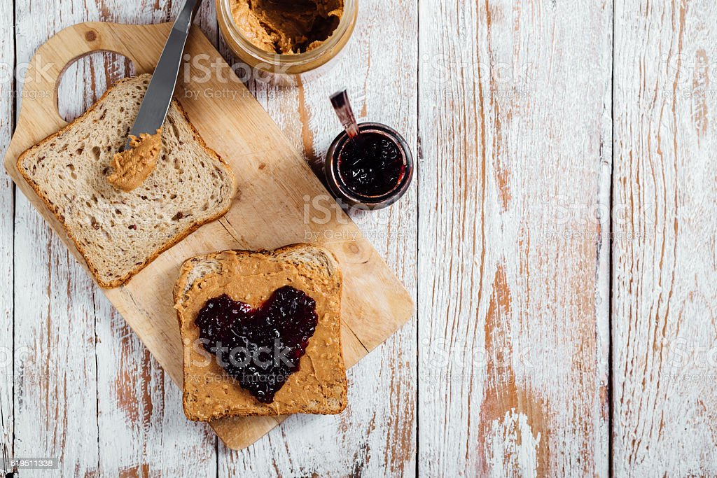 Homemade peanut butter and jelly sandwich on wooden background stock photo
