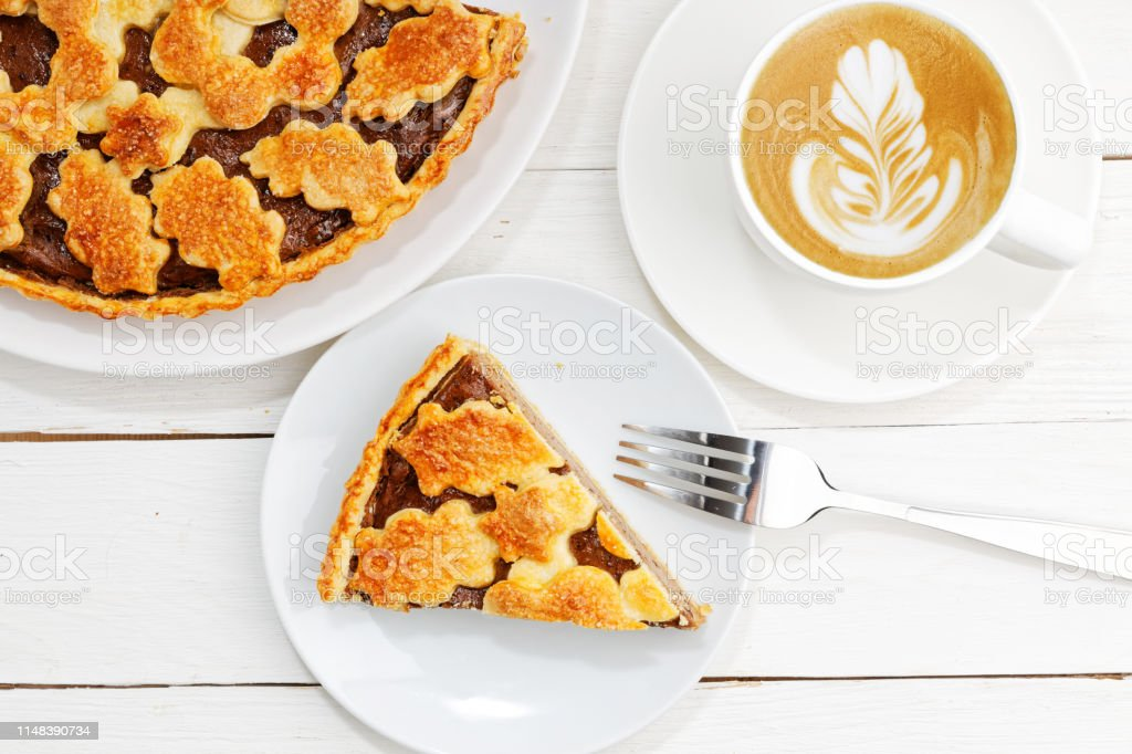 Homemade pie with cottage cheese and prunes and cup of coffee. Top...
