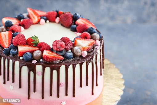 480972628 istock photo Homemade pink cake decorated with chocolate and  fresh berries 673158970