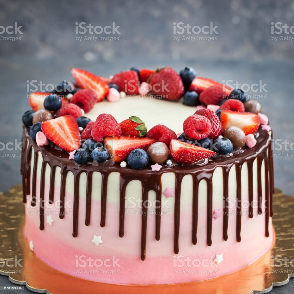 Homemade pink cake decorated with chocolate and  fresh berries stock photo