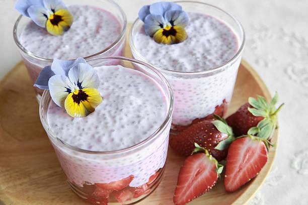 hausgemachte pink chia pudding mit erdbeeren und essbare blumen - chia pudding kokosmilch stock-fotos und bilder