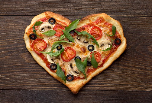 Homemade pizza in heart shape with chicken and mushrooms on rustic wooden table.