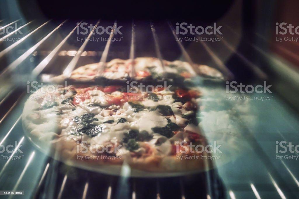 Hausgemachte Pizza wird in einem modernen Elektro-Backofen gebacken. – Foto
