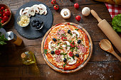 istock Homemade Pizza on wooden board, with tomatoes and salami, mushrooms, Italian style on old wooden table, top view 1165206740