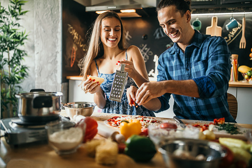 Photo of young couple preparing pizza at home