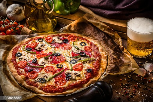 High angle view of a homemade pizza  made with salami, mozzarella, mushrooms, cherry tomatoes, black olives and green bell pepper alongside a drinking glass full of beer and some ingredients. Low key DSLR photo taken with Canon EOS 6D Mark II and Canon EF 24-105 mm f/4L