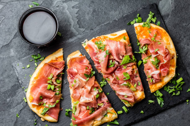 Homemade pizza with jamon serrano served on slate plate with glass of red wine stock photo