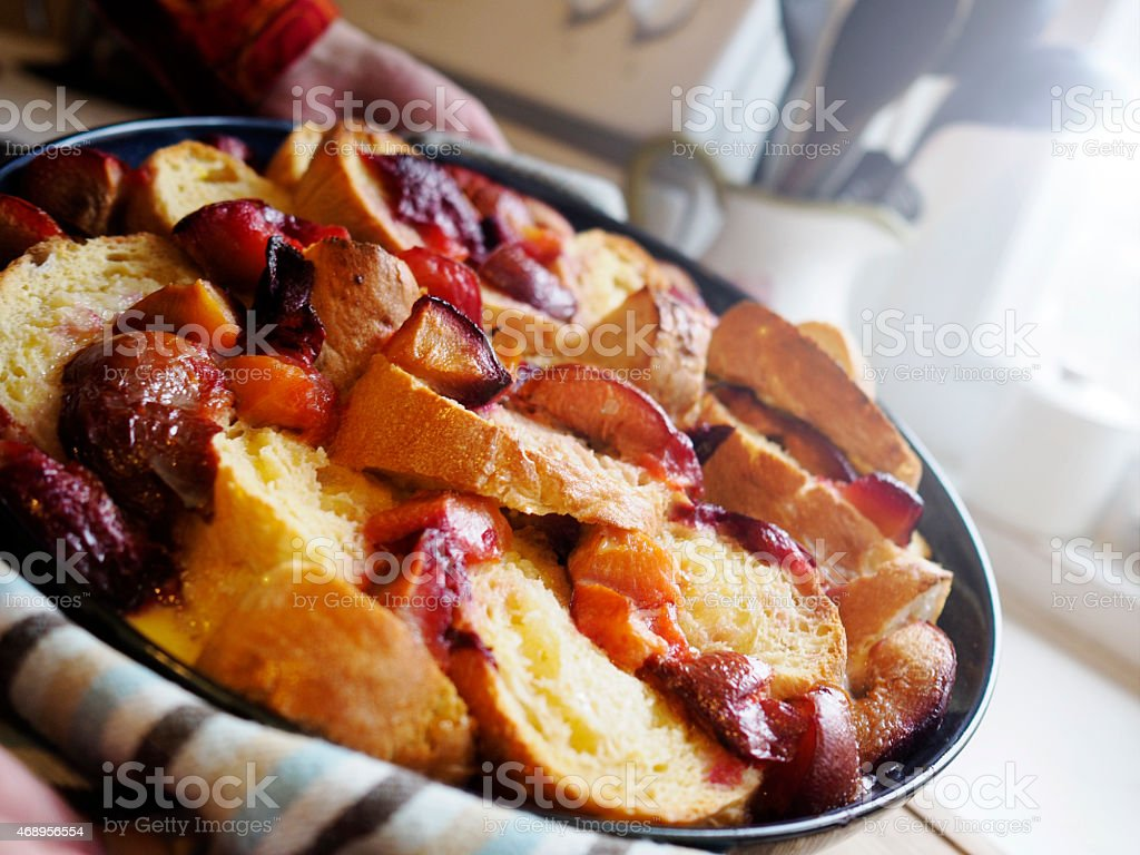 Homemade plum, bread and butter pudding in a woman's hands stock photo