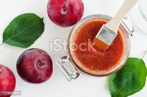 istock Homemade plum face mask in a glass jar. DIY cosmetics and spa recipe. Top view, copy space. 1174419928