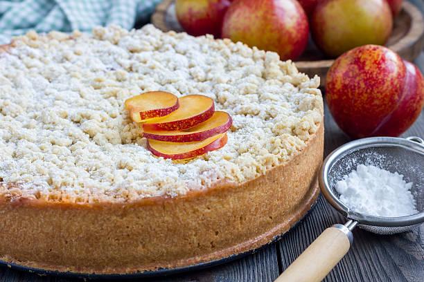 homemade plum shortbread pie with streusel on wooden table - crumble deutsch stock-fotos und bilder