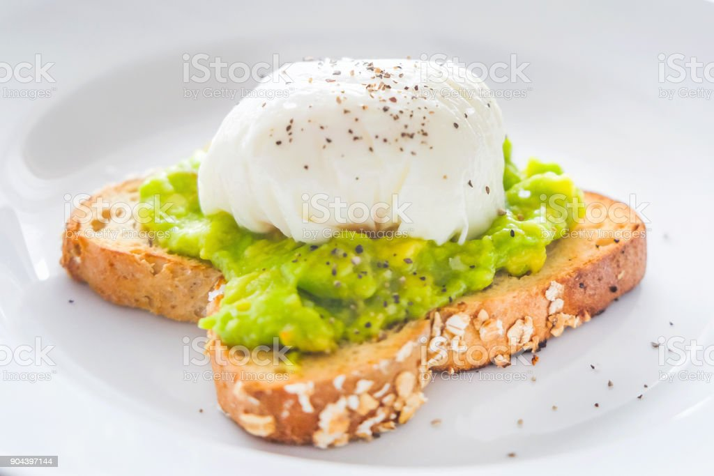 Homemade poached eggs with smashed avocado stock photo