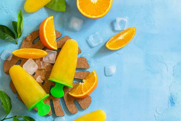 오렌지 주스, 과일 얼음, 푸른 돌이나 슬레이트 배경에 사탕과 홈 메이드 아이스캔디. 상단보기 평면 누워 배경입니다. 공간을 복사합니다. 스톡 사진