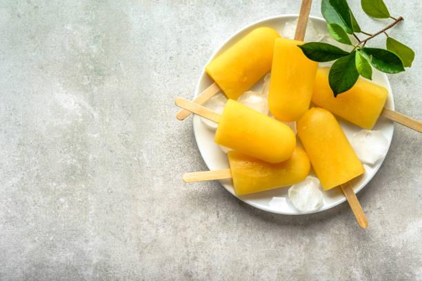 hausgemachte eis am stiel mit orangensaft, eis am stiehl auf sticks, ansicht von oben flach zu legen - mango eis am stiel stock-fotos und bilder