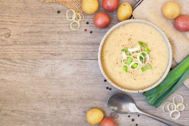 Homemade potato and leek soup, top view table scene on light wood with copy space Homemade potato and leek soup. Top view table scene on a light brown wood background with copy space. leek stock pictures, royalty-free photos & images