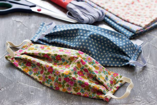 hausgemachte schutzmaske und stoffstücke auf grauem hintergrund. - textilien stock-fotos und bilder