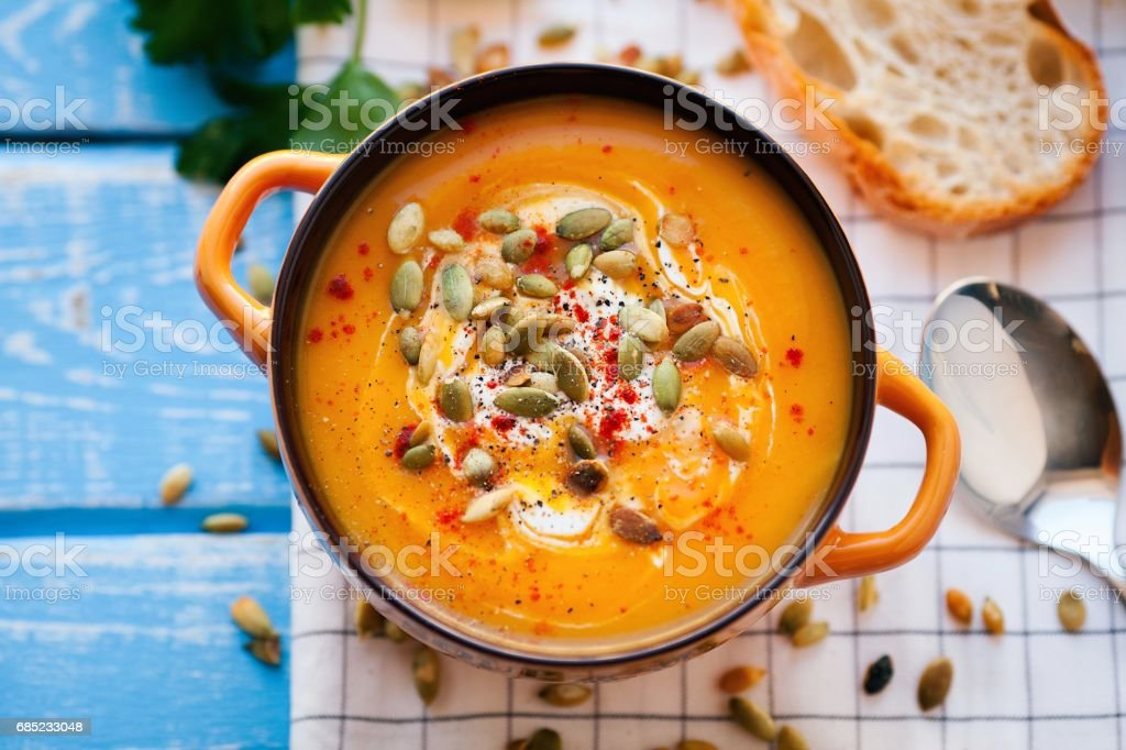 Homemade pumpkin soup with cream, bread, greens and pumpkin seeds on a wooden background. Top viev royalty-free stock photo