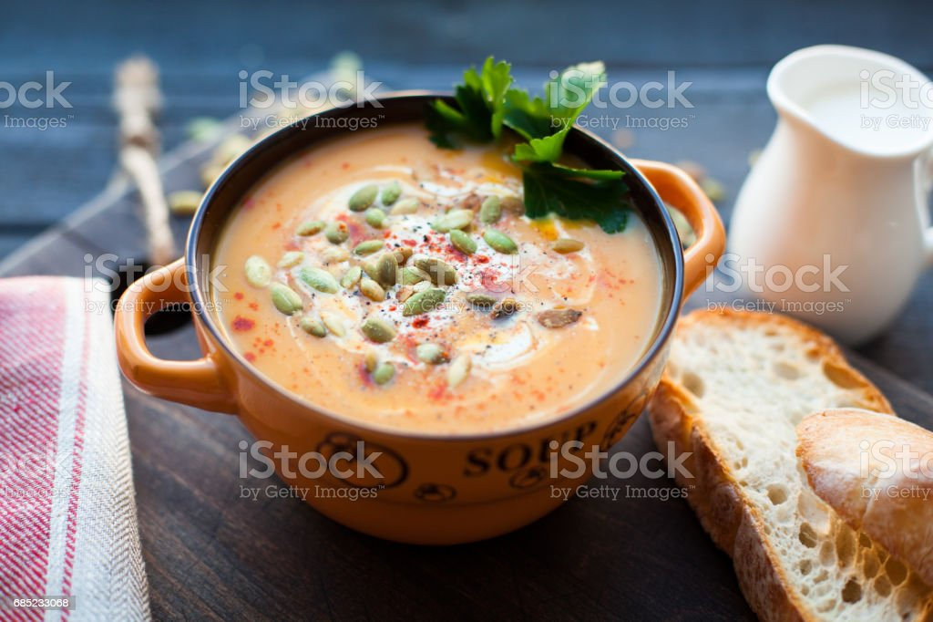 Homemade pumpkin soup with cream, bread, greens and pumpkin seeds on a wooden background. Top viev foto de stock royalty-free