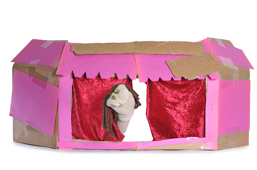 Homemade cardboard puppet theater isolated on a white background. The theater is crudely assembled and authentically created by children. There is one sock puppet preforming.