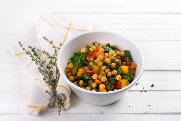 Hausgemachtes Ragout mit Kürbis, Karotten, Paprika, Tomaten, Kichererbsen, Grünkohl und Thymian in einer Schüssel weiß auf weißem Hintergrund – Foto