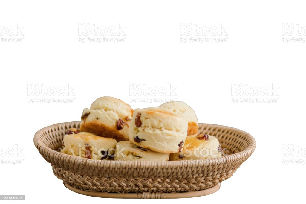 Homemade raisin scones in basket with white isolated background and clipping paths. Scones is traditional English pastry so delicious for afternoon tea or coffee break. Homemade bakery concept. stock photo